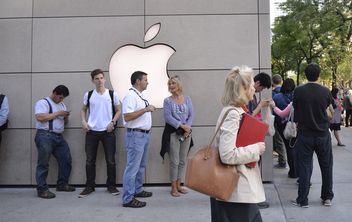 Customers lining up outside an Apple store.